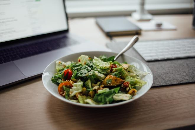 A mixed salad on a desk with a computer screen in the background