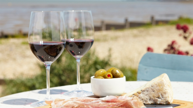 Two glasses of red wine on a table with the beach in the background